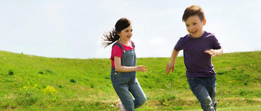dečak i devojčica trče po livadi